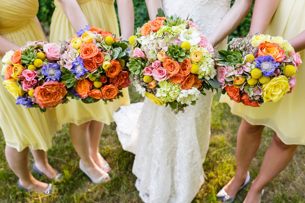 Bouquets of succulents, pink and orange roses, yellow Ranunculus, and blue-purple Scabiosa (Pin Cushion Flower). The large white flower in the bride's bouquet is white Scabiosa.