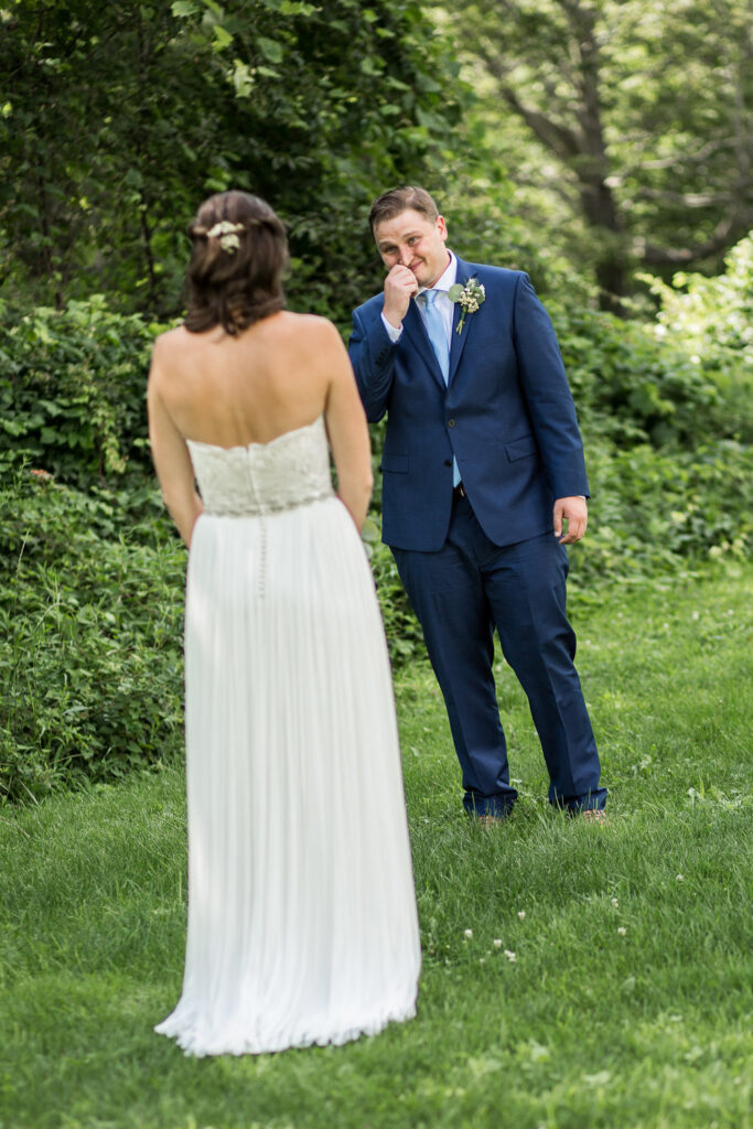 groom's first look at his bride, wearing a BHDLN dress at Bunnell Farm wedding venue in MA