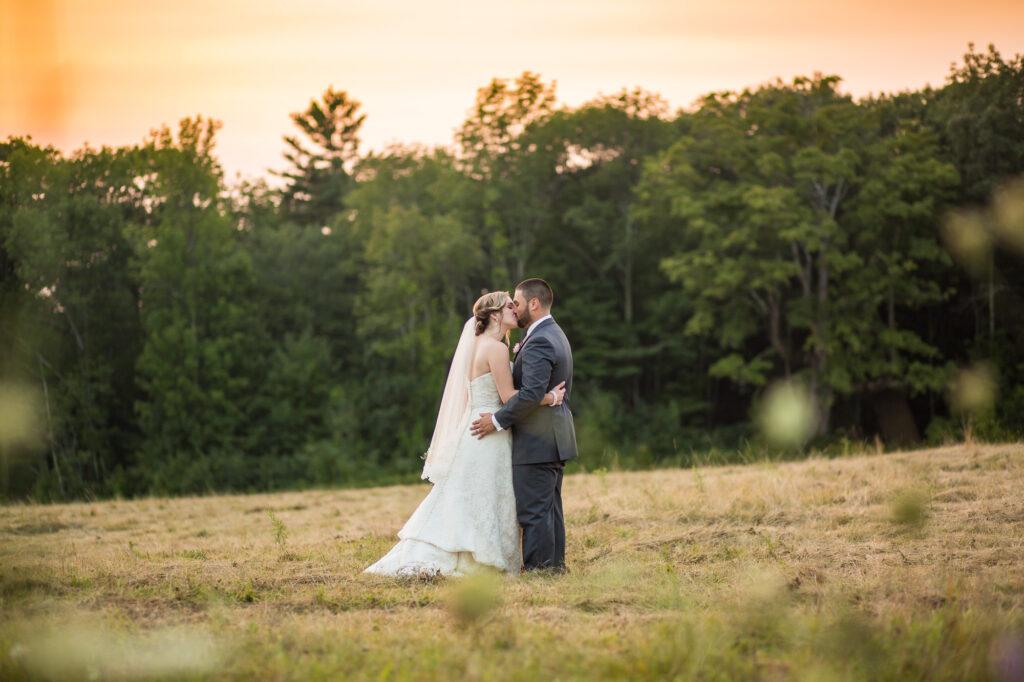 bride and groom portrait sunset in hay field at Harrington Farm