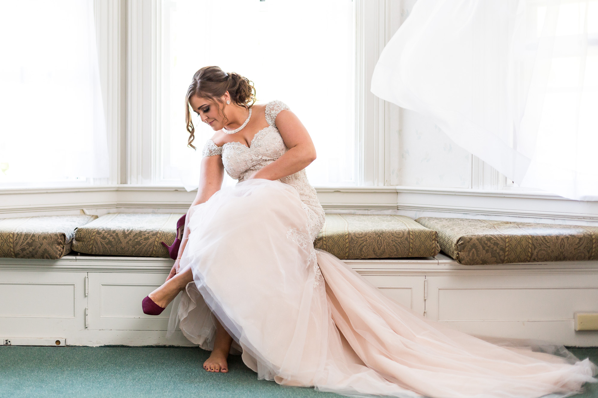 bride at Mansion at Bald Hill putting on shoes for natural bridal portrait