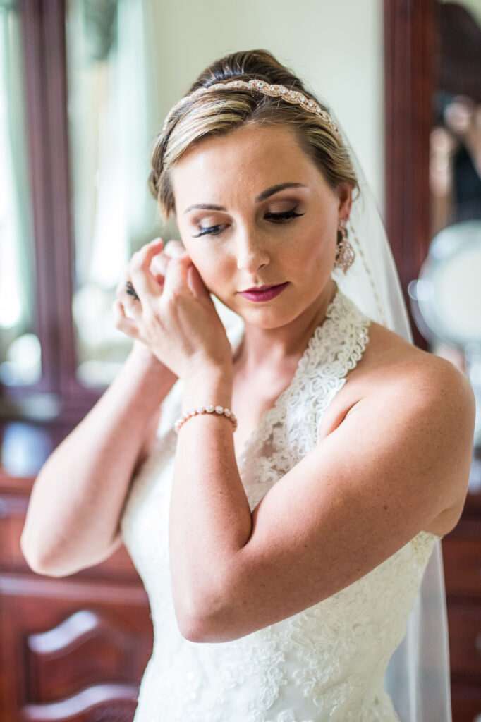 natural photo of bride putting on earrings
