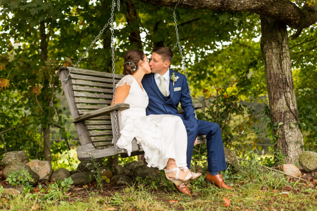 bride and groom kissing on a swing on their wedding day at Priam Vineyards