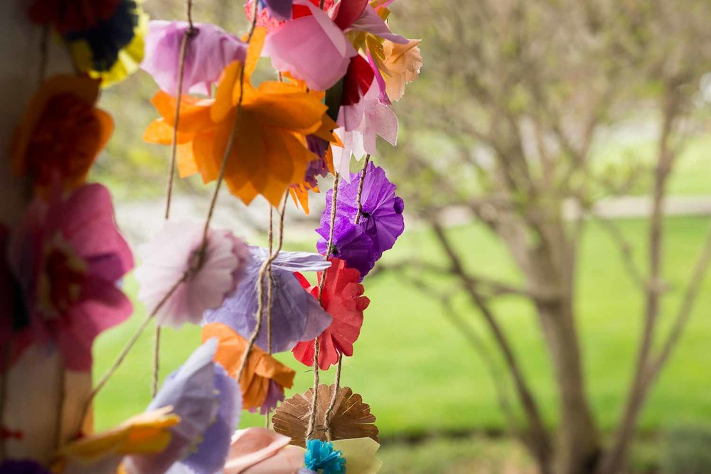 Strings of handmade paper flowers as a bright wedding decoration