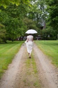 bride walking to her first look holding a white umbrella at Tyrone Farm