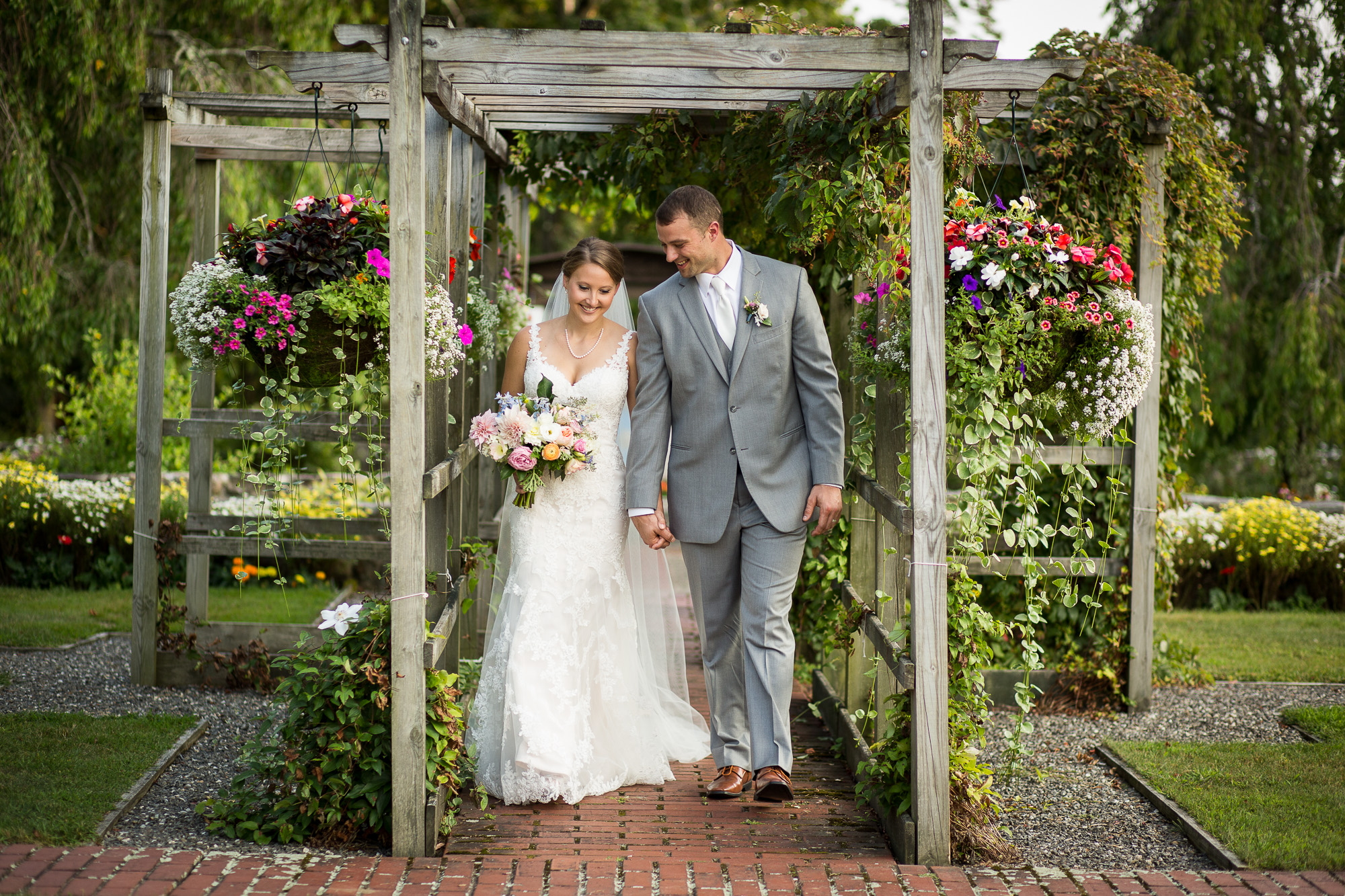 bride and groom walking through arbor at Mansion at Bald Hill garden