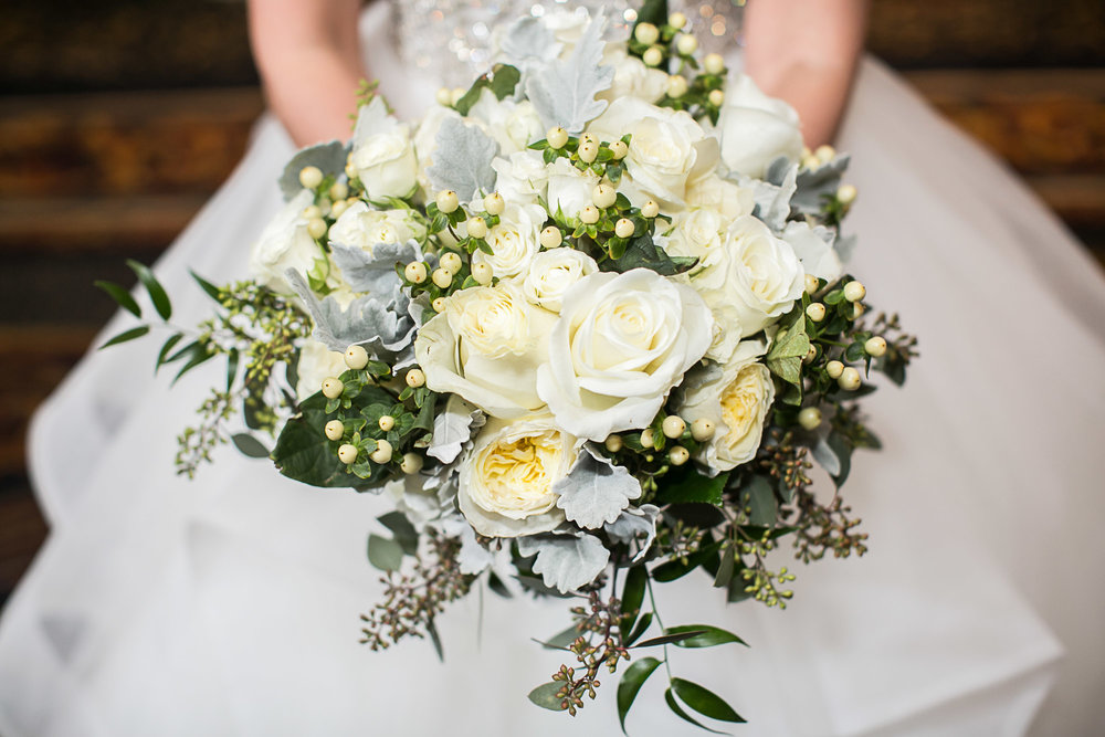 Here is a winter bouquet full of white roses and berries, with some Israeli ruscus, and seeded eucalyptus which looks like lilac before blooming.