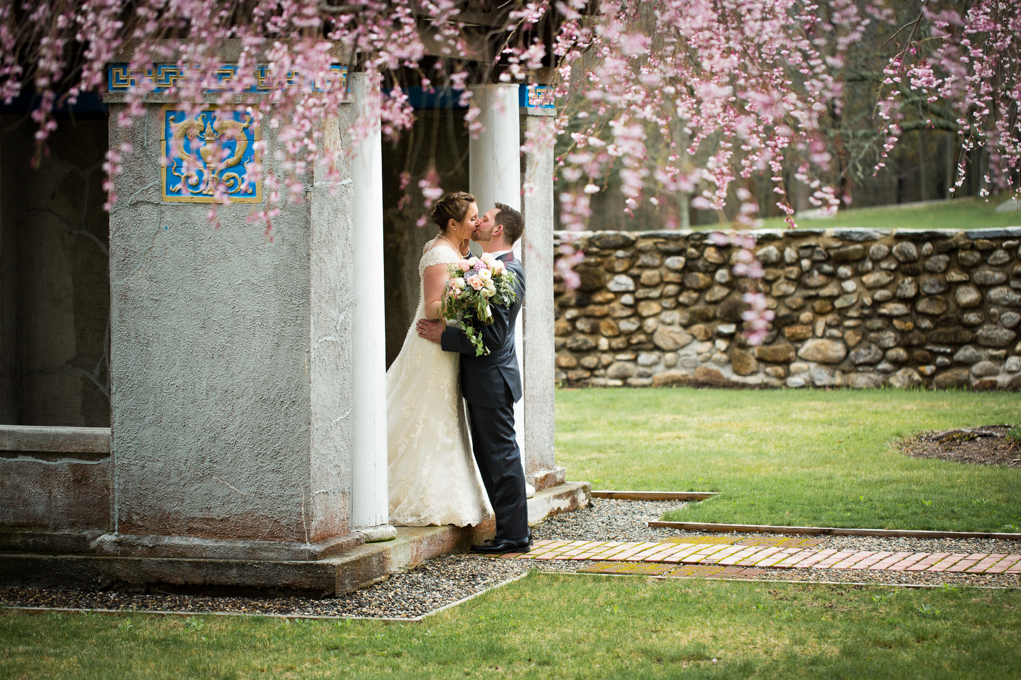 bride and groom kissing for portraits at garden ceremony area at Mansion at Bald Hill