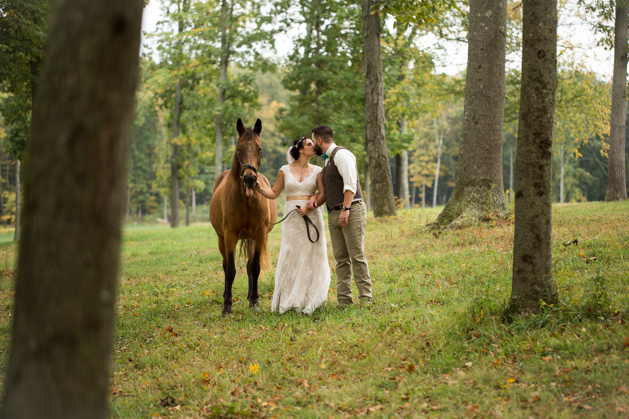 bride and groom kissing in the forest at Candlelight Farms inn, with the horse