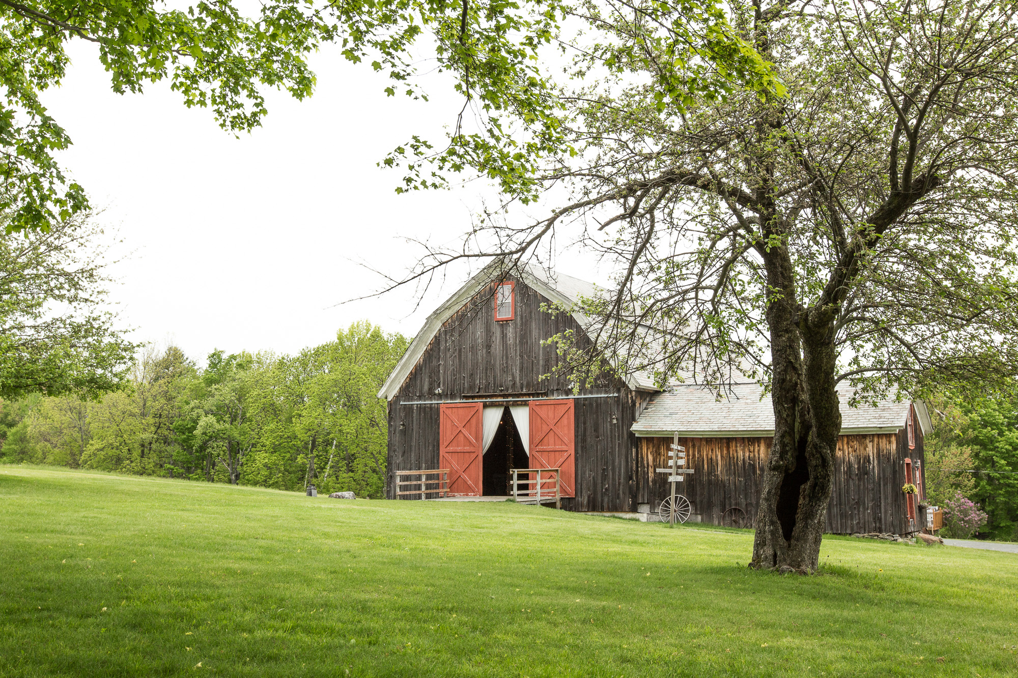 distant view of Bliss Farm's rustic barn and red doors