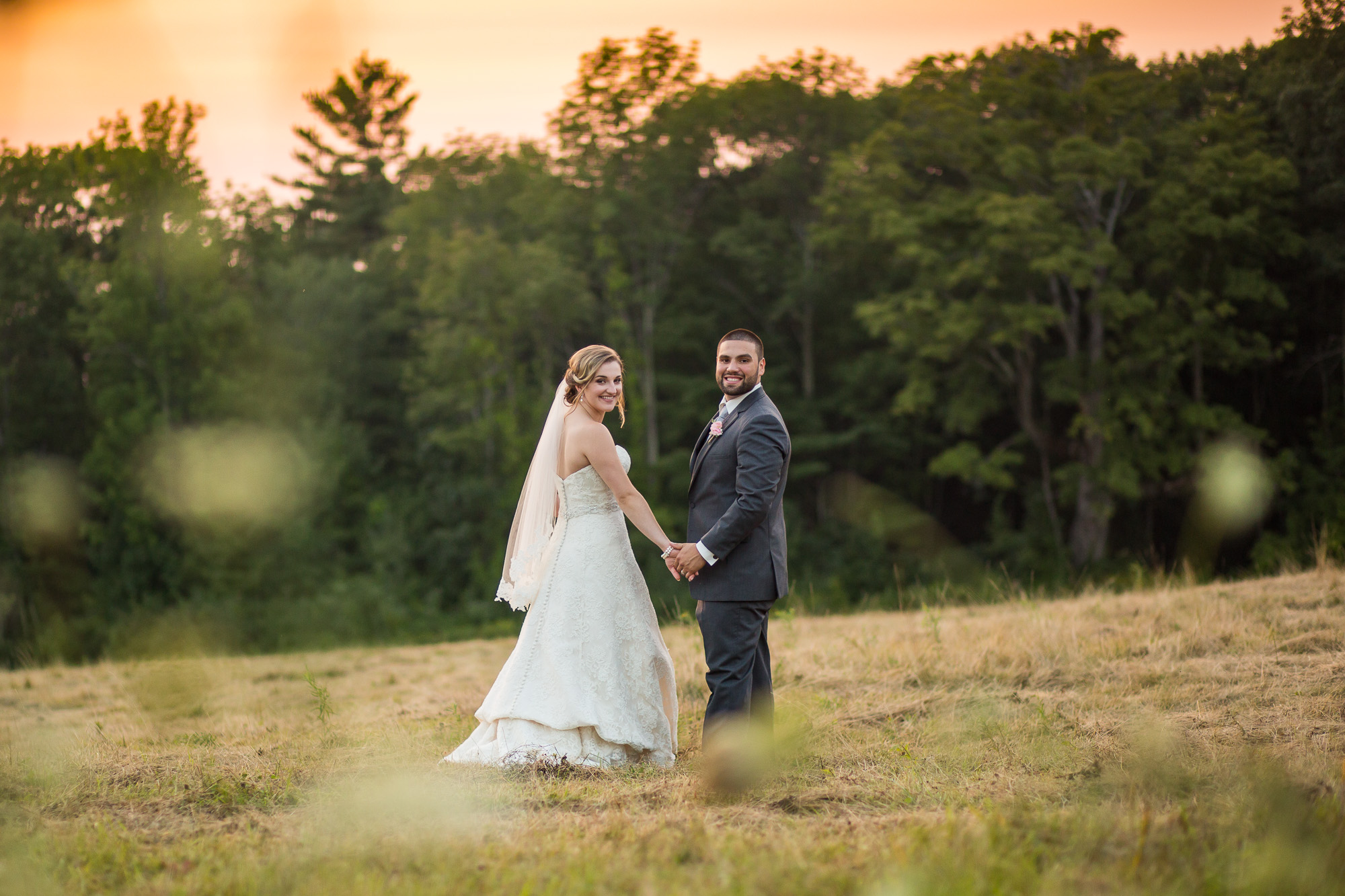 bride and groom in a wildflower hay field at Harrington Farm in MA, at sunset