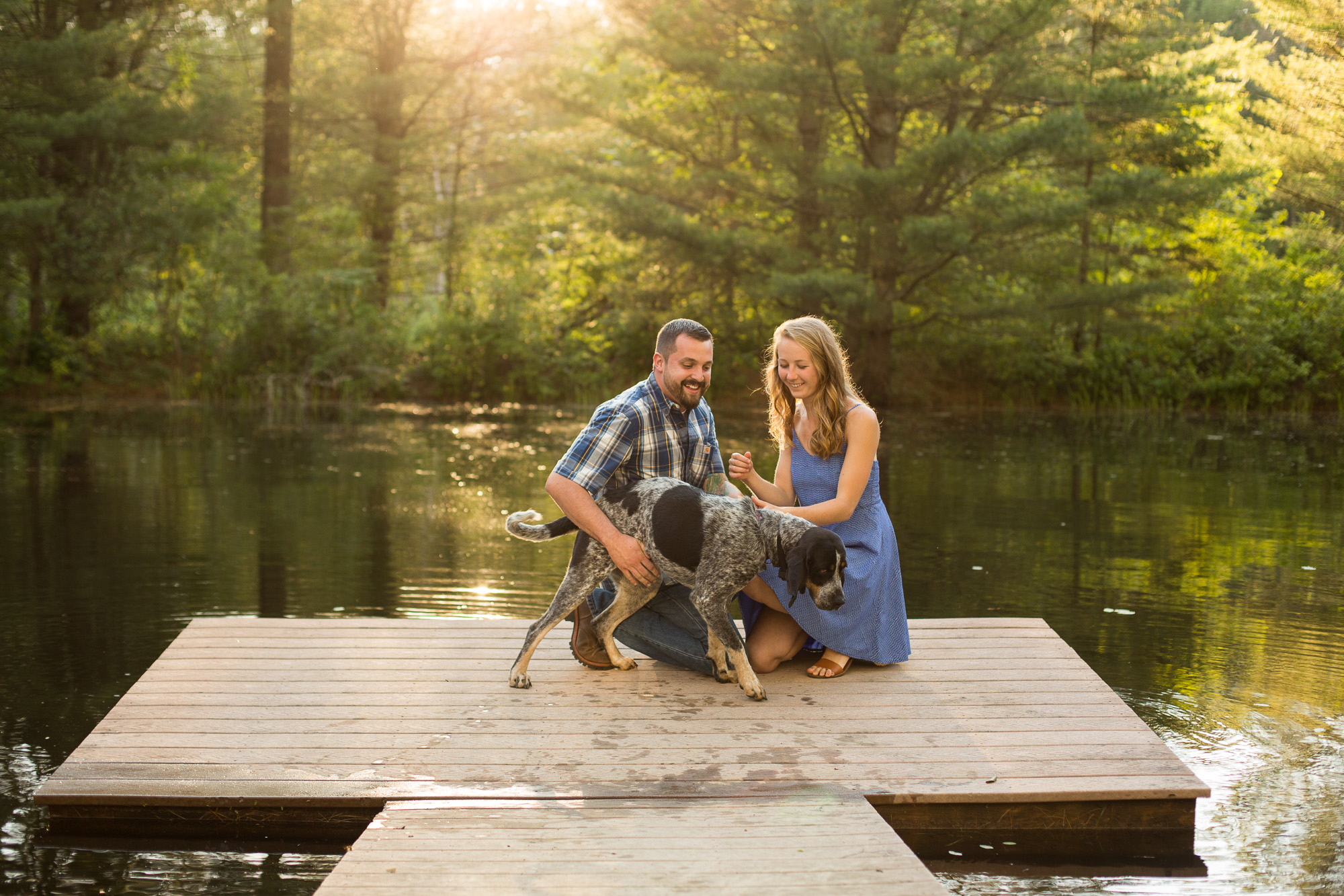 blue tick coon hound with engaged couple on the dock