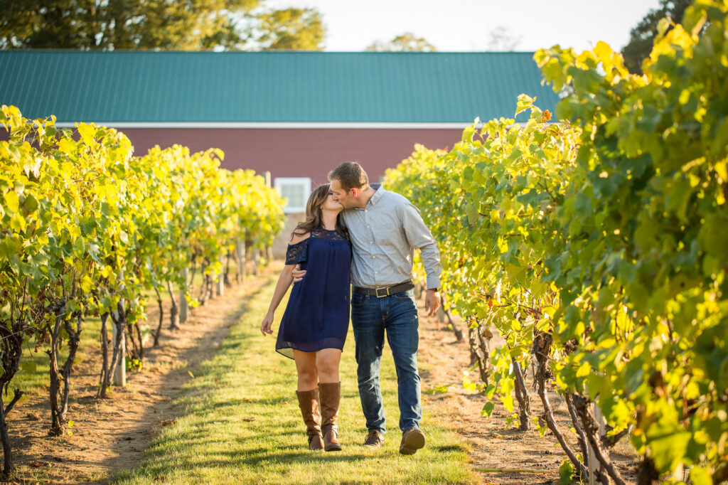 couple kissing at Rosedale Vineyard with barn in distance