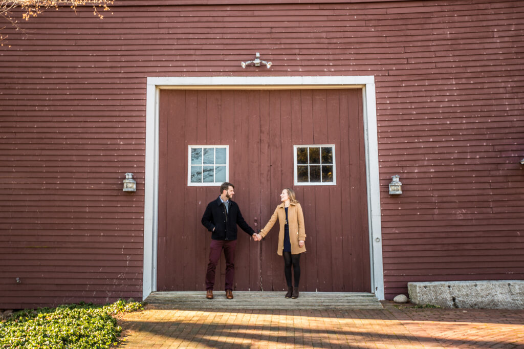 engaged couple standing holding hands in front of barn doors at Tyrone Farm in Pomfret